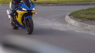 The biker rides around the city on a motorcycle blue-yellow motorcycle slowe motion