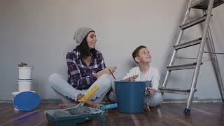 The boy and his mother are sitting on the floor, looking at the room that they just painted in gray color and joyfully giving five to each other. End of working day, work completed slow votion