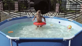 The boy floats on an inflatable pool in the pool slow motion