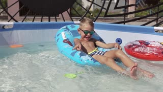 The boy is having fun swimming in the pool slow motion