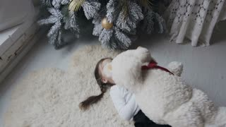 The charming girl lies on a soft white carpet and is played with a large plush bear. Winter holidays. Christmas tree slow motion