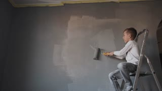 The child sits on the ladder in the room and draws the wall with a roller a gray color . The guy whitewash the wall in a new room. Happy boy paint the room slow motion