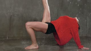 The dancer performs a dance piece on the floor under the spray of water rain. The wet girl performs a dance in a red sweater and shorts under the rain in the studio, slow motion