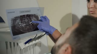 The dentist-woman shows the patient an x-ray for further treatment of the teeth. Dentistry. Dentist shows a young man's ill tooth on a radiograph 4K