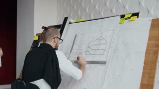The designer and engineer stand next to the drawing instrument with the project and solve important issues in the construction of a residential building 4k