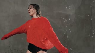 The girl dances in the rain. Wet female dancer in a red sweater circles around himself under the drops of rain. Modern dance, slow motion