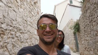 The happy young family is walking in the historic European streets of the old city. Beautiful family travels to Croatia. Tourists explore the city's architectural sights. slow motion
