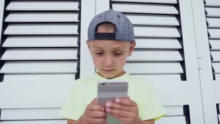 The kid in cap and t-shirt is holding a smartphone in front of him and concentrated playing video game, on a white background. Cute boy in t-shirt and cap playing online games on smartphone isolated