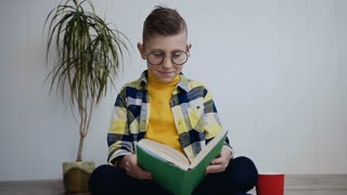 The nice little school boy in glasses reading funny a book, drinks drink with the red cup while sitting on the floor in white indoor. He dressed yellow blouse, plaid shirt and dark pants slow motion