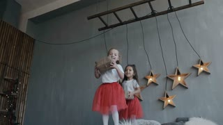 The two little sisters of the twin actively have fun at the bed of their parents. Children dressed in identical red skirts, jump on the bed with Christmas gifts in their hands slow motion