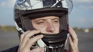The young biker wearing a helmet for riding a motorcycle. Close up slow motion