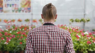The young gardener goes to a flower shop and sets flowers. Slow motion.
