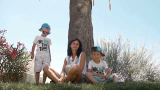 The young mother and her little sons, have fun sitting under the palm trees and hiding from the burning sun. Fun holidays slow motion