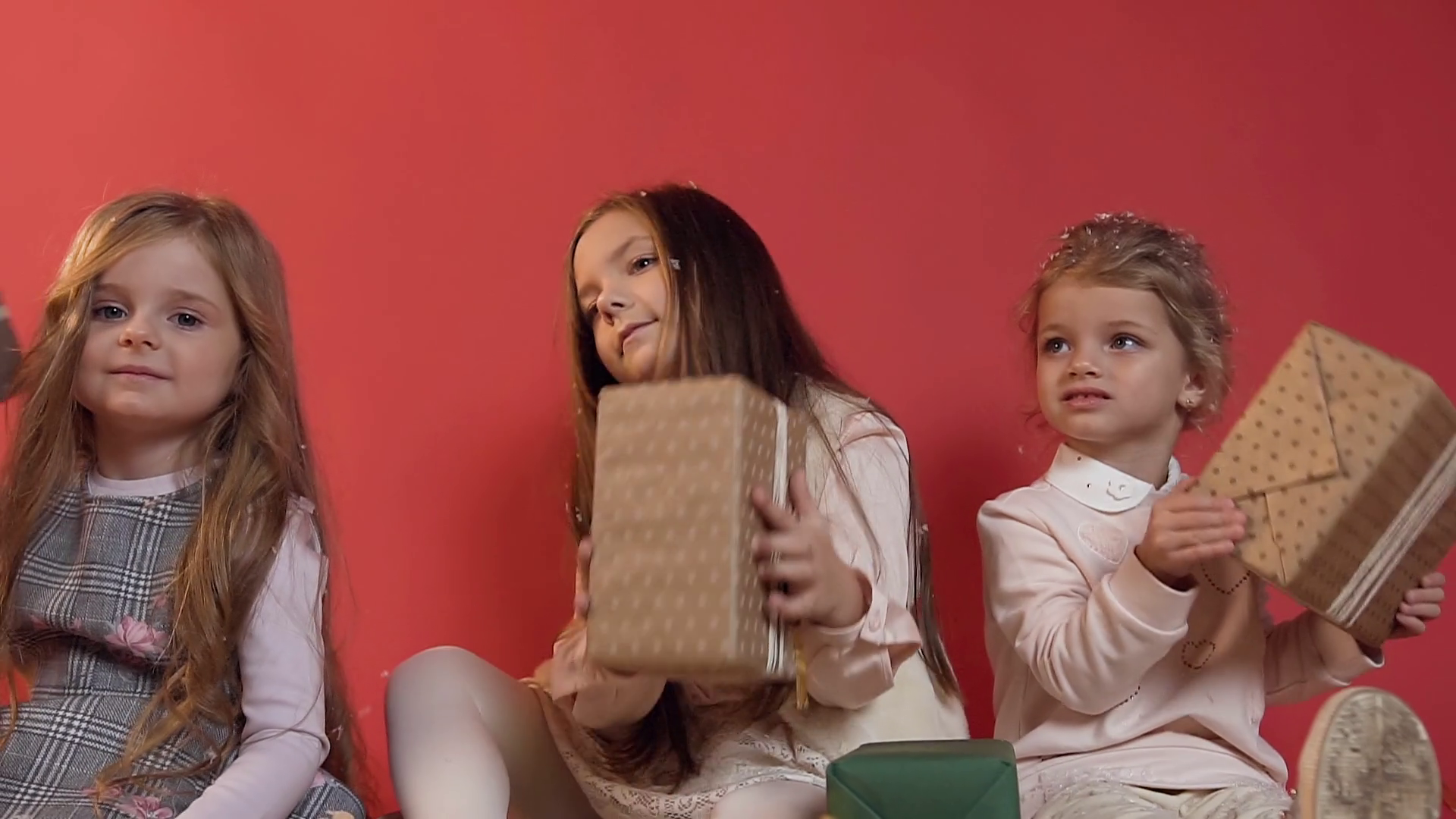 Three cute happy little models sitting on the floor on the red background and playing with well packed presents Stock Video Footage - Storyblocks
