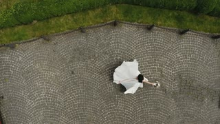 Top view. A beautiful bride in the nature spins around herself and holds a bouquet in her hand. Wedding day slow motion