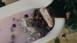 Top view. A beautiful young woman reads a book and relaxing in a warm bath filled with milk and fragrant flower buds. Beautiful woman relaxing in milk bath lying in bathtub while reading an