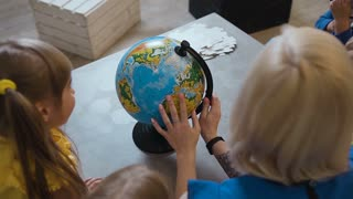 Top view. A stylish teacher with a tattoo shows the kids a globe. Teacher discussing over a globe with kids in geography classroom at elementary school, slow motion