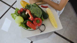 Top view. The two sisters on a wooden board cut pepper chili and avocado for cooking the salad at the kitchen table. Cutting peppers and avocado, slow motion