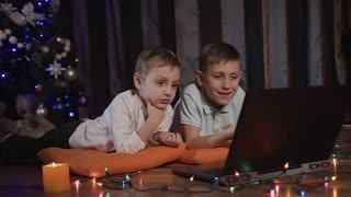 Two beautiful little guys are lying on orange decorative pillows on the floor in the living room and watching a cartoon on a laptop through a social network. On the floor in front of the children laid