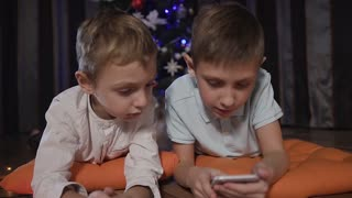 Two children lie on ornate orange pillows on the floor near the Christmas tree. The older brother uses the mobile phone for the online game, the younger one - watches how the elder brother plays slow