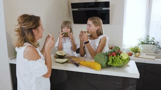Two cute teens sisters and an their mom in white clothes eat ripe melon at the kitchen table at home. Healthy food, diet, vegan, slow motion