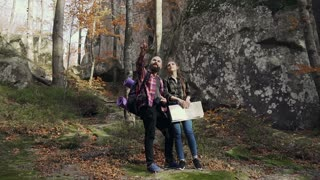 Two friends are a man and a woman enjoying views of the mountain rush. Young man and woman stand in the mountains at high rocks and look at their looks slow motion