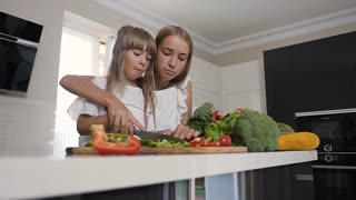 Two girls in white dresses are cutting vegetables at home in the kitchen. Two charming girls preparing salad. Attractive teen sisters cooking healthy vegetarian salad together in kitchen, slow motion