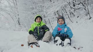 Two little kid boys in colorful clothes sitting outdoors in forest during snowfall. Active leisure with children in winter on cold days. Happy brothers and a happy winter holiday slow motion