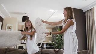 Two sister in white dress jump on the sofa have fun fighting with soft pillows in the living room at home. Two cute teenage girls have fun with white pillows at studio apartment, slow motion