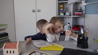 Two small beautiful children have fun and talk on the phone using a free internet network. The guys use the phone using a free internet network slow motion