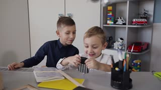 Two small children sitting at the table in the white room and have fun using the free internet network through the wireless connection in the phone slow motion