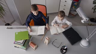 Two students do homework at home. The guys draw designs for houses that are on their table. Two junior schoolboys doing lessons at home slow motion