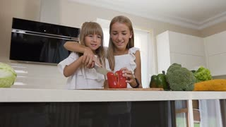 Two teen girls in white dress cook in the kitchen: The girls cuts red peppers to make a salad. Older sister teaches the younger sister to cut paprika. The girls prepare vegetable salad at home in the