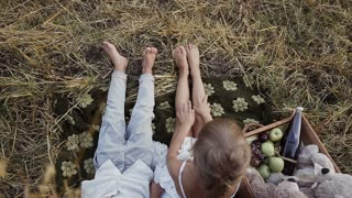 Two young children sit in a field under bale of straw with bare feet. A boy with a girl eat fruit slow motion