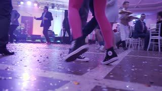 UKRAINE, LVIV - JAN 18, 2018: Close-up dancing of young people, legs male and female dancing at disco party dressed in sneakers slow motion