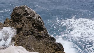 Waves crashing over rocks in summer day. Adriatic sea, slow motion