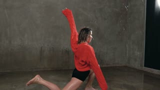 Wet girl dancer in red sweater and black shorts performs contemporary dance in the rain and splashes of water. Professional dancer who danced under the water during the dance in indoors before studio
