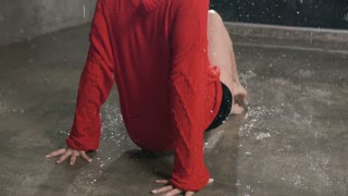 Wet young woman in red sweater and black shorts is dancing on the floor under the rain and splashes of water. Drops water, rain, contemporary dance, slow motion