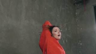 Wet young woman is practicing in dance studio under rain water, before studio light. Workout of he young girl in indoors under the drops rain. A young girl performs a jump while dancing, slow motion