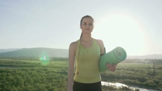 Young athlete girl walking to do morning practice on outdoor. Young sports woman holding green yoga mat. Workout on a summer day at sunset, slow motion