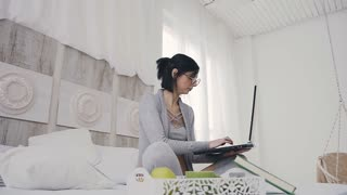 Young attractive brunette woman sitting in lotus position on the bed in white bedroom with laptop dark. Beautiful girl in glasses typing text on a laptop at home in the room slow motion
