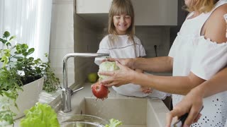 Young beautiful mom and her lovely two daughters together wash the vegetables in the kitchen sink getting ready to cook salad for lunch. They dressed in white clothes. Atractive woman with her