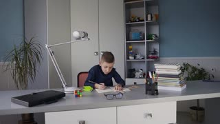 Young cute boy in a blue shirt sitting at a desk in his room and doing a homework. Books on the table, homework slow motion