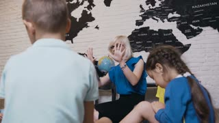 Young female teacher teaching figure giving math lesson to little boys and girls in kindergarten. The teacher taugh t to count of their little pupils in elementary school, 4k