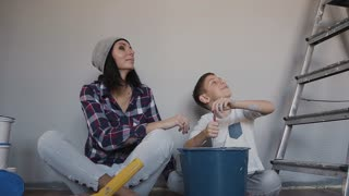 Young girl and her brother finished doing repairs in the room, they are happy with the result and they give five to one another in the hands. Relatives sit on the floor next to the ladder near the