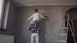 Young mother holds her son in her arms and the son paints a top wall with a roller in a gray color. Sister and brother draw wallpaper on the wall in gray color slow motion