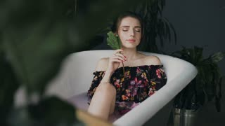 Young sexy woman relaxing in a hot bath at spa center. Beautiful girl in bath with fragrant flowers relaxing with eyes closed. Body care and spa treatments, 4k