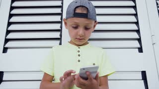 Young teenager in cap playing game on smartphone, isolated on white door background. Child playing with smartphone technology. Close-up of young boy who write message on his smartphone, slow motion