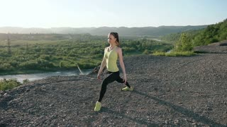Young woman warming up before fitness workout at sunrise in the morning. Girl stretching outdoors. Female runner doing stretching exercise before running outdoor in the mountain, slow motion
