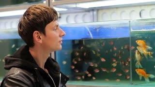 A buyer looking at aquarium fish in a pet store